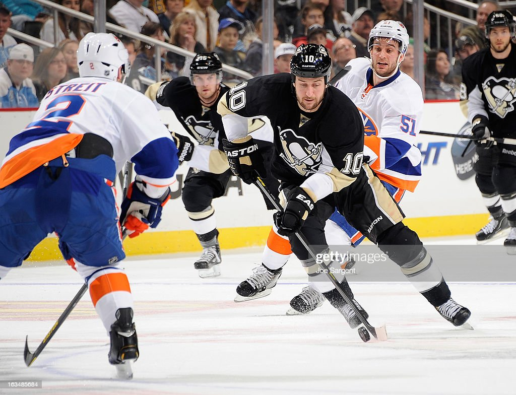 <a gi-track='captionPersonalityLinkClicked' href=/galleries/search?phrase=Tanner+Glass&family=editorial&specificpeople=4596666 ng-click='$event.stopPropagation()'>Tanner Glass</a> #10 of the Pittsburgh Penguins moves the puck up ice between the defense of <a gi-track='captionPersonalityLinkClicked' href=/galleries/search?phrase=Mark+Streit&family=editorial&specificpeople=636976 ng-click='$event.stopPropagation()'>Mark Streit</a> #2 and <a gi-track='captionPersonalityLinkClicked' href=/galleries/search?phrase=Frans+Nielsen&family=editorial&specificpeople=634894 ng-click='$event.stopPropagation()'>Frans Nielsen</a> #51 of the New York Islanders on March 10, 2013 at Consol Energy Center in Pittsburgh, Pennsylvania. Pittsburgh won the game 6-1.