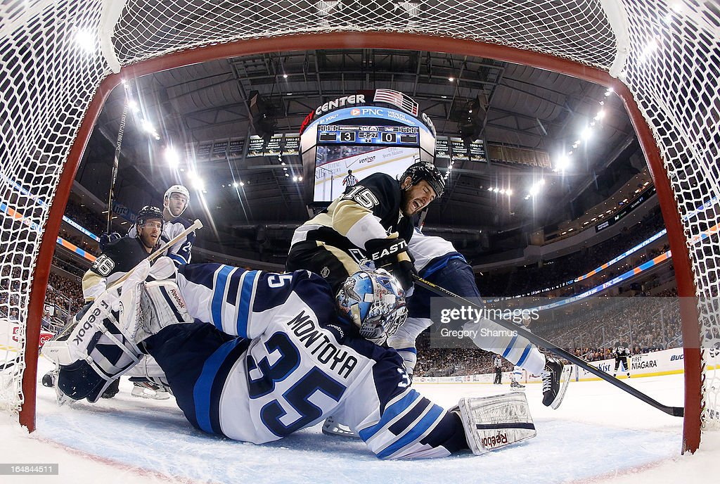 Tanner Glass #15 of the Pittsburgh Penguins reaches for the loose puck in front of Al Montoya #35 of the Winnipeg Jets on March 28, 2013 at Consol Energy Center in Pittsburgh, Pennsylvania.