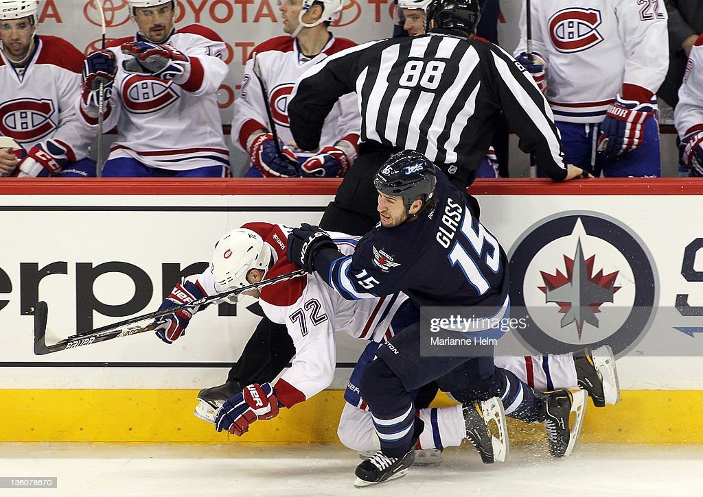 <a gi-track='captionPersonalityLinkClicked' href=/galleries/search?phrase=Tanner+Glass&family=editorial&specificpeople=4596666 ng-click='$event.stopPropagation()'>Tanner Glass</a> #15 of the Winnipeg Jets and <a gi-track='captionPersonalityLinkClicked' href=/galleries/search?phrase=Erik+Cole&family=editorial&specificpeople=204754 ng-click='$event.stopPropagation()'>Erik Cole</a> #72 of the Montreal Canadiens collide into linesman Mike Cvik in NHL action at the MTS Centre on December 22, 2011 in Winnipeg, Manitoba, Canada.