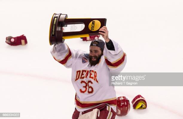 Tanner Jaillet of the Denver Pioneers celebrates a victory against the Minnesota Duluth Bulldogs by raising the championship trophy after the 2017...
