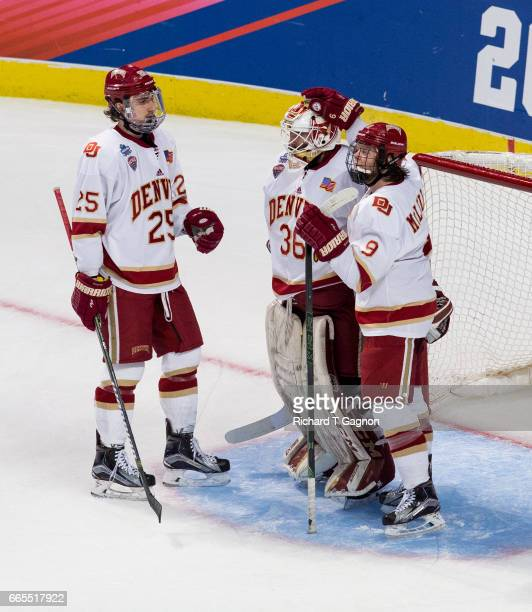 Tanner Jaillet of the Denver Pioneers celebrates a victory with teammates Blake Hillman and Tyson McLellan during game two of the 2017 NCAA Division...