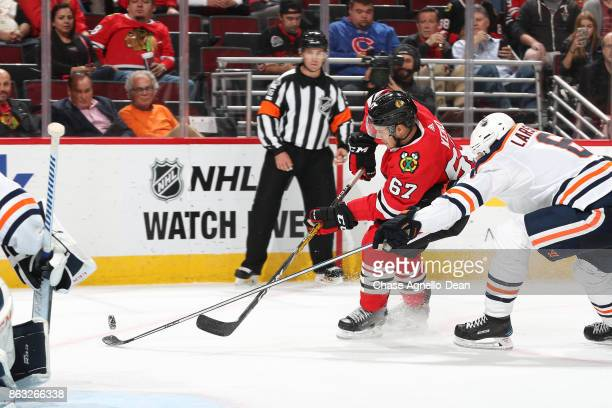 Tanner Kero of the Chicago Blackhawks and Adam Larsson of the Edmonton Oilers chase the puck in the second period at the United Center on October 19...
