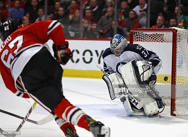Tanner Kero of the Chicago Blackhawks scores a goal against Connor Hellebuyck of the Winnipeg Jets at the United Center on January 26 2017 in Chicago...