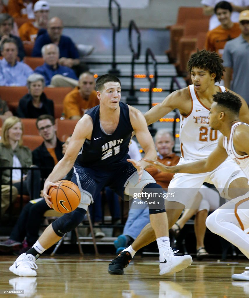 Tanner Leissner #21 of the New Hampshire Wildcats drives against Jericho Sims #20 and Eric Davis Jr. #10 of the Texas Longhorns at the Frank Erwin Center on November 14, 2017 in Austin, Texas.