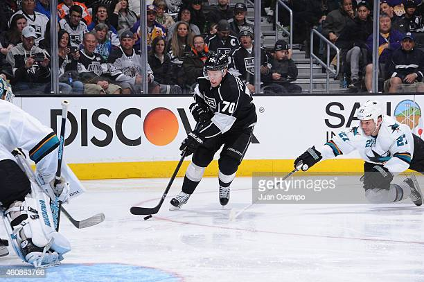 Tanner Pearson of the Los Angeles Kings handles the puck against Scott Hannan of the San Jose Sharks at STAPLES Center on December 27 2014 in Los...