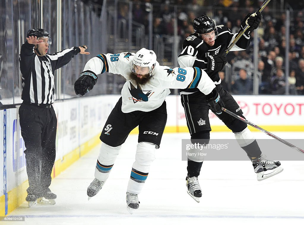 Tanner Pearson #70 of the Los Angeles Kings takes a check from Brent Burns #88 of the San Jose Sharks during the second period at Staples Center on November 30, 2016 in Los Angeles, California.