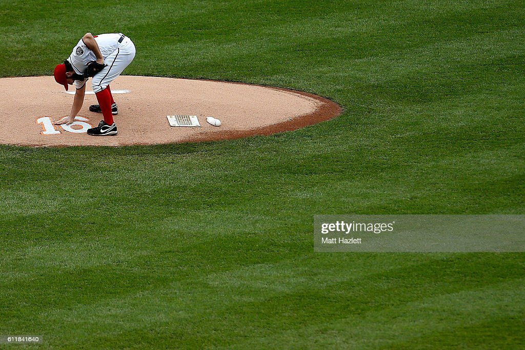 Tanner Roark #57 of the Washington Nationals touches a number 16 memorializing Miami Marlins pitcher Jose Fernandez, who died in a boating accident, on the pitchers mound in the first inning against the Miami Marlins at Nationals Park on October 1, 2016 in Washington, DC.