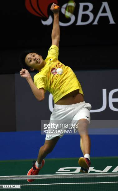 Tanongsak Saengsomboonsuk of Thailand hits a return against Sai Praneeth of India during their men's singles quarterfinal match at the Singapore Open...