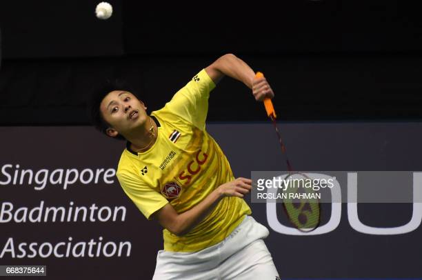 Tanongsak Saengsomboonsuk of Thailand plays a shot against Sai Praneeth of India during their men's singles quarterfinal of the Singapore Open...