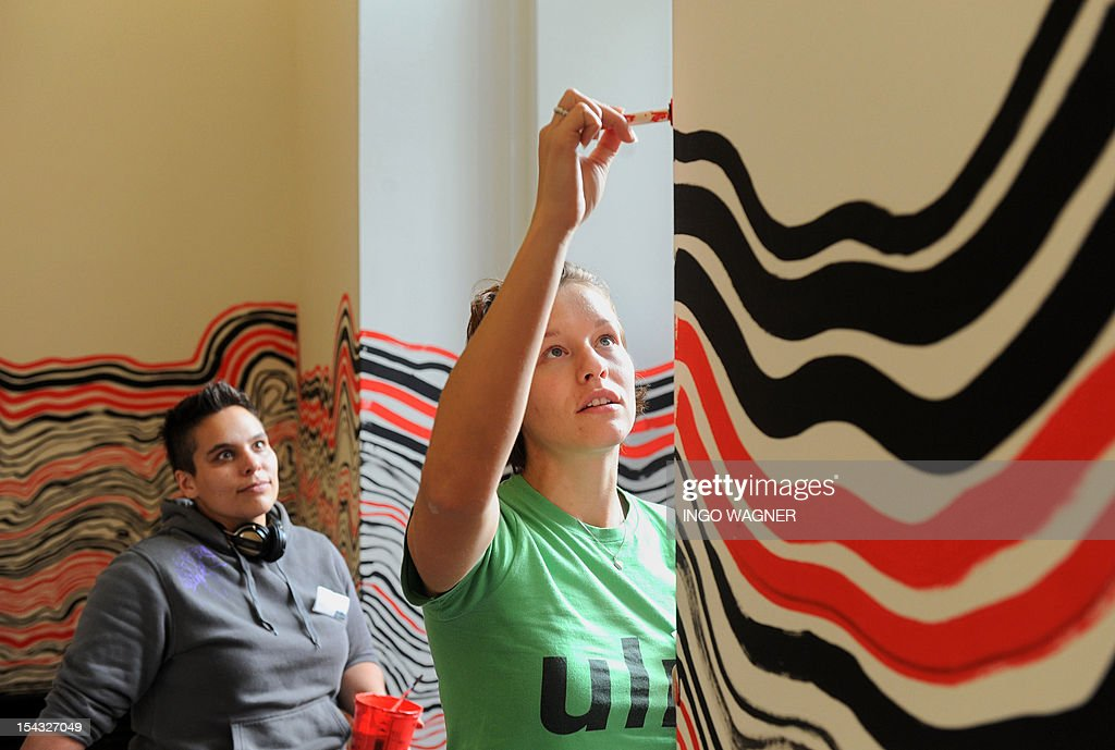 Tanya Bora (L) and Nora Grimm, students of the University of the Arts Bremen, draw the 'Linie des Lebens' (Line of Life) on October 18, 2012 at the Kunsthalle Bremen museum in Bremen, northern Germany. The 50 hours long action is a remake of 'The Hamburg Line' performance that Austrian artist Friedensreich Hundertwasser and other artists staged together with students in 1959, when they covered the walls of Hundertwasser's studio with an endless line. The legendary 1959 event is considered to be an hour of birth for European Performance Art and Happening and is re-staged now in connection with the show 'Friedensreich Hundertwasser: Against the Grain. Works 1949-1970', that is running from October 20, 2012 to February 17, 2013 at the Kunsthalle Bremen museum. AFP PHOTO / INGO WAGNER GERMANY OUT