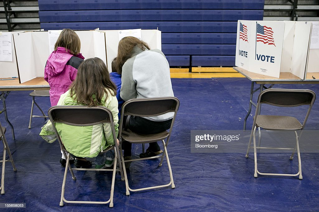 Tanya Paiva fills out a ballot with her children at a polling station in Manchester, New Hampshire, U.S., on Tuesday, Nov. 6, 2012. U.S. President Obama is seeking to overcome the drag of high unemployment and economic weakness that has frustrated predecessors' re-election bids, while his Republican rival Mitt Romney reaches for an upset to propel him beyond his party's standing and swamp an electoral map stacked against him on the final day of the presidential race. Photographer: Andrew Harrer/Bloomberg via Getty Images