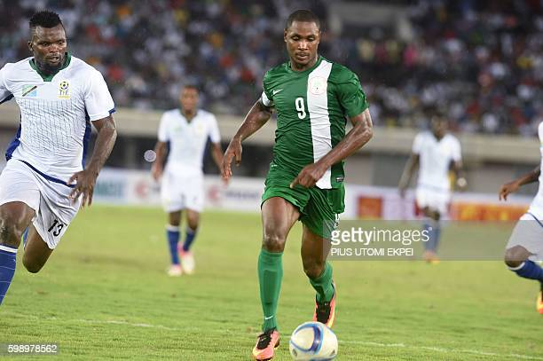 Tanzanian defender David Mwantika chases Nigerian attacker Odion Ighalo during the Africa Cup of Nations qualification match between the two Nigeria...