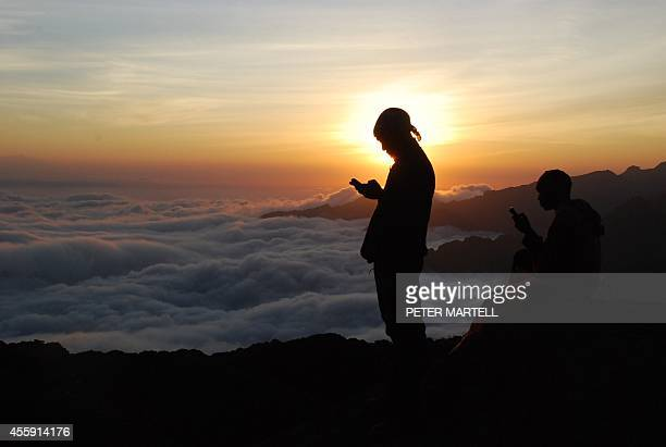 Tanzanian porters and guides stand on a rock half way up Kilimanjaro at sunset on September 21 2014 trying to get a mobile phone signal to call their...