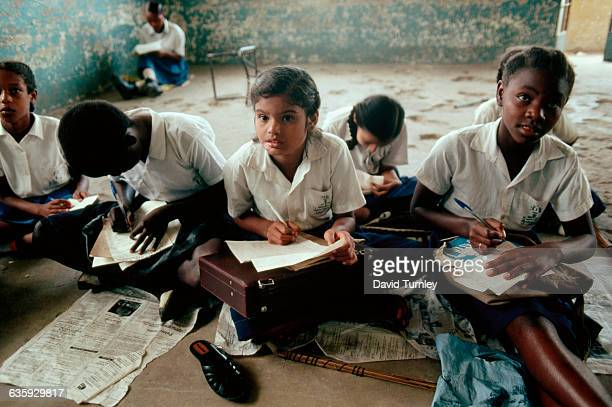 Tanzanian school children take notes while sitting on the floor of their classroom