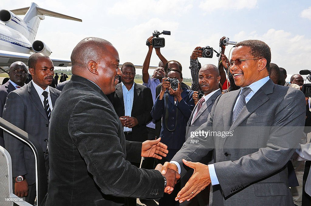 Tanzania's President Jakaya Kikwete (R) meets with Democratic Republic of Congo's (DRC) President, Joseph Kabila (L) at Dar es salaam airport on January 30, 2013. Kabila, according to the Tanzanian state house is in Dar es salaam for a one day visit for consultations with Kikwete. The United Nations (UN) wants to set up an intervention force to fight rebels fuelling conflict in DRC. Tanzania is the only country which has offered troops so far. AFP PHOTO/John Lukuwi