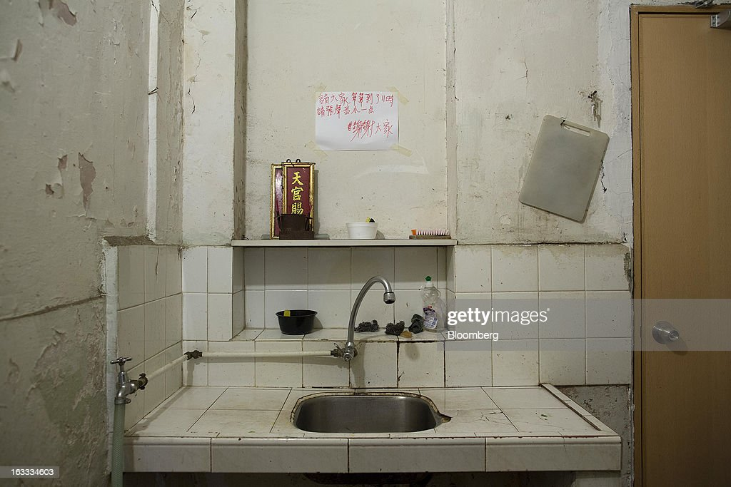 A taoist altar sits on a shelf behind a kitchen sink in an apartment partitioned into cubicle apartments in Sham Shui Po district in Hong Kong, China, on Thursday, Jan. 24, 2013. Hong Kong's GDP expanded 2.5 percent last quarter from a year earlier, the most in a year, a bright end to what was the weakest annual expansion since 2009. Photographer: Jerome Favre/Bloomberg via Getty Images