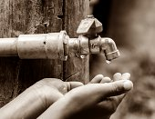 Water dropped from the old tap on hand in dry season, rural area Thailand.