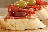 selection of spanish meat with olives on sliced crusty bread