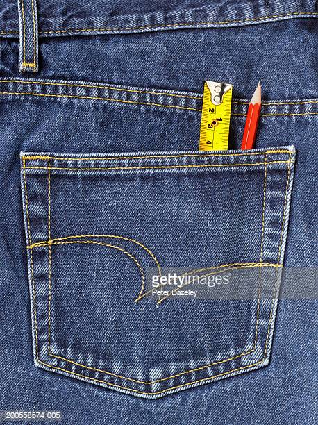 Tape measure and pencil sticking out of back pocket of jeans, close-up