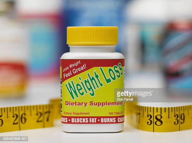 Tape measure beside weight loss dietary supplement