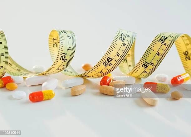 Tape measure, pills and capsules, studio shot