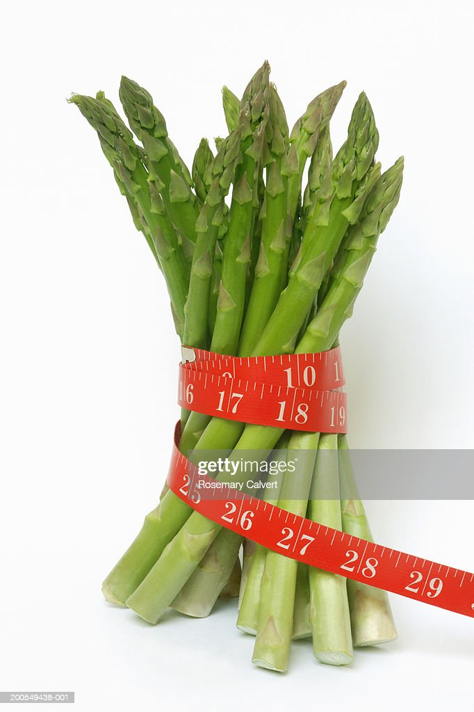 Tape measure wrapped around bunch of asparagus, close-up : Stock Photo