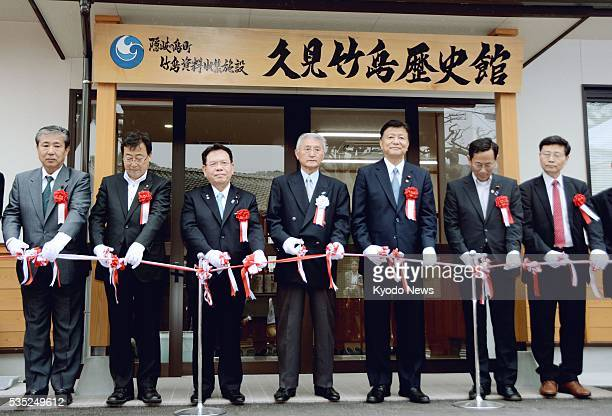 A tapecutting ceremony is held in the western Japan town of Okinoshima on May 29 ahead of the June 1 opening of the Kumi Takeshima History Museum...
