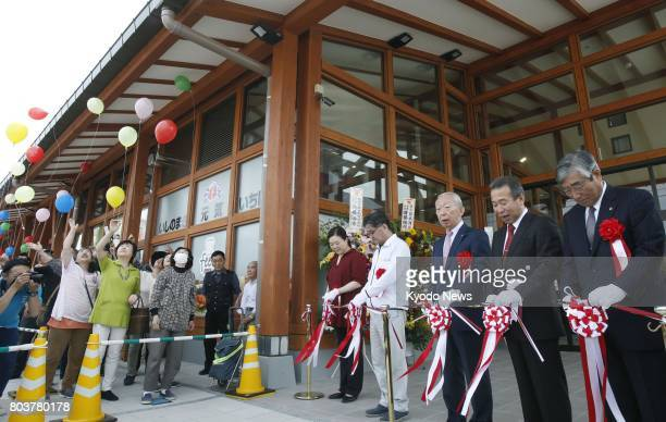 A tapecutting ceremony is held to mark the opening of the new Ishinomaki Genki Market shopping center in the tsunamihit northeastern Japan city of...