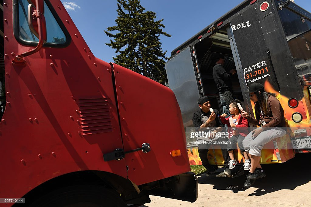JT Tapia, far left, enjoys a popsicle with his son Jobe, 5, middle and wife Dawn Marie, right, as he takes a break from working at Wheels On Fire, a wood-fired food truck, at Civic Center Park on the first day of the 11th annual Civic Center EATS on May 3, 2016 in Denver, Colorado. This is metro Denver's largest gathering of gourmet food trucks and carts and is a showcase of Denver's culinary and entrepreneurial diversity. The daily food truck lunch event runs through October 6th from 11 am to 2 pm Tuesdays, Wednesdays and Thursdays.