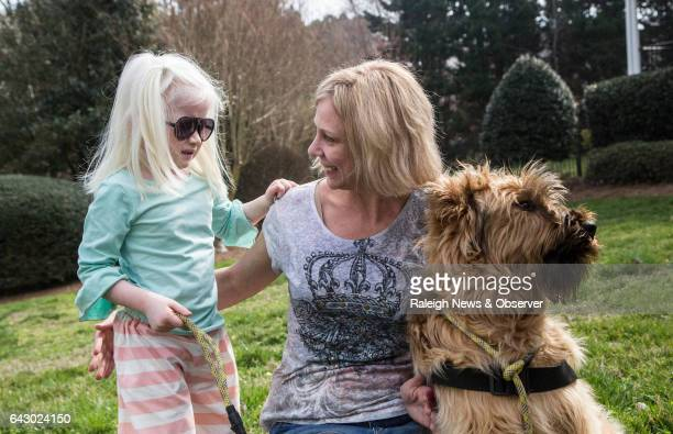 Tara Deane and her 4yearold adopted daughter Eliana who has albinism autism and is partially sighted train with Eliana's servicedogintraining Butters...