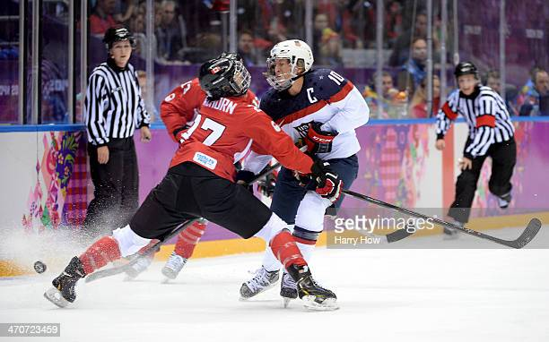 Tara Watchorn of Canada checks Meghan Duggan of the United States during the Ice Hockey Women's Gold Medal Game on day 13 of the Sochi 2014 Winter...