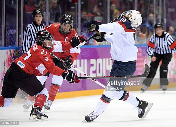 Tara Watchorn of Canada trips Meghan Duggan of the United States during the Ice Hockey Women's Gold Medal Game on day 13 of the Sochi 2014 Winter...