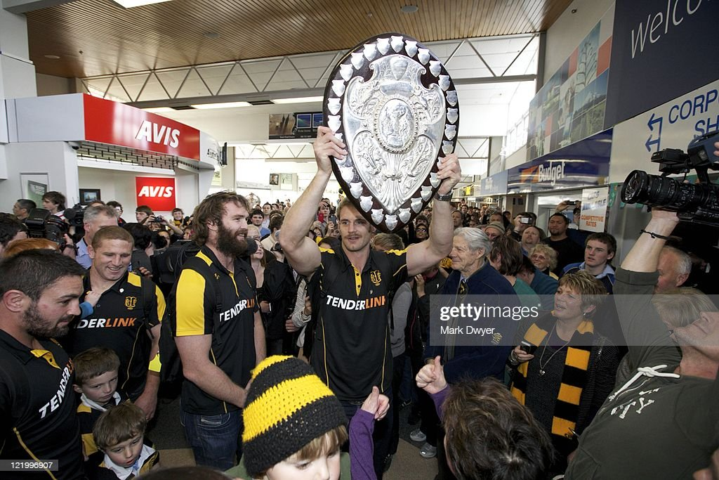 Taranaki rugby team captain Craig Clark holds the Ranfurly Shield as players arrive at New Plymouth airport with the Ranfurly Shield on August 25...