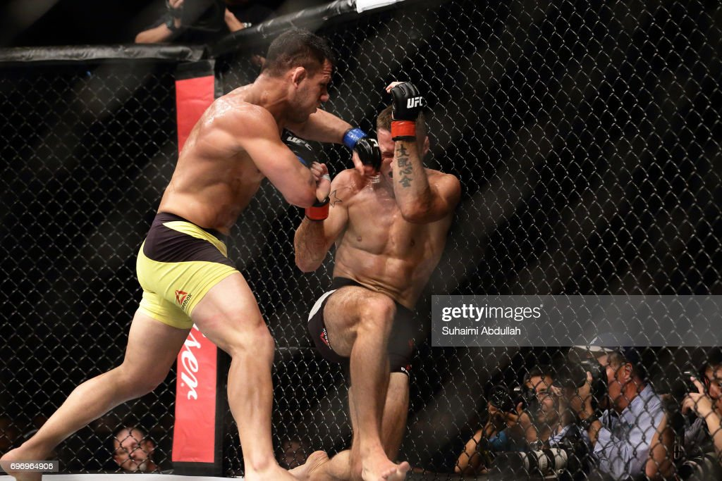 Tarec Saffiedine of Belgium (R) fights Rafael dos Anjos of Brazil (L) in the Welterweight Bout during UFC Singapore Fight Night at Singapore Indoor Stadium on June 17, 2017 in Singapore.