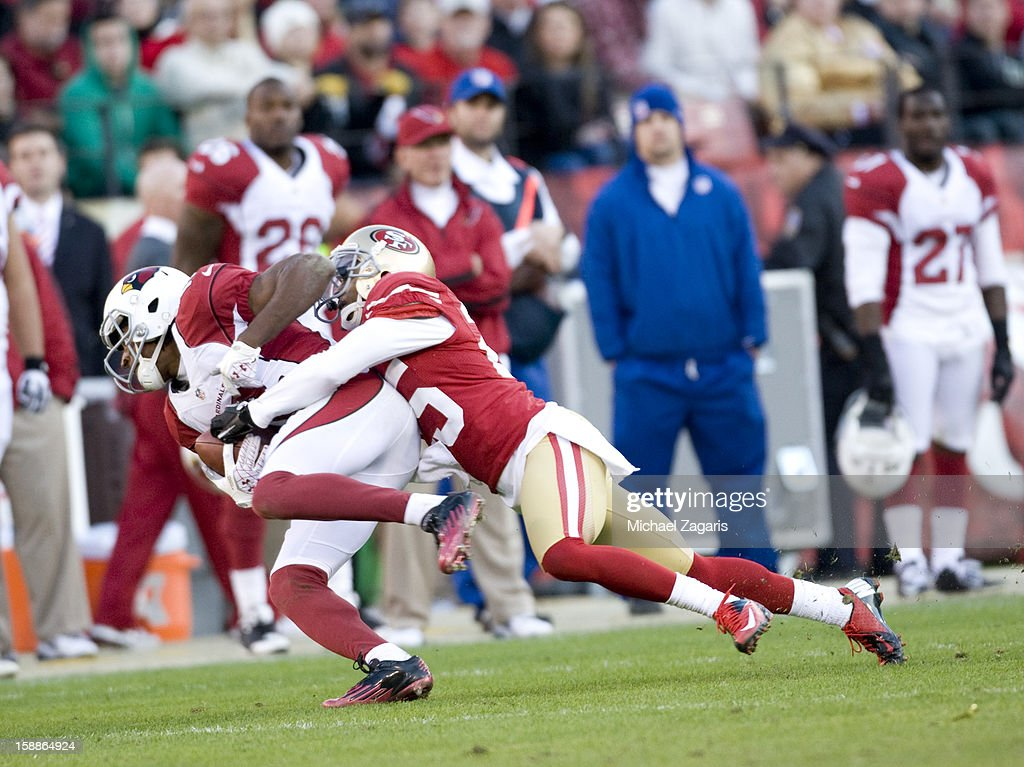 Tarell Brown #25 of the San Francisco 49ers tackles Larry Fitzgerald #11 of the Arizona Cardinals during the game at Candlestick Park on December 30, 2012 in San Francisco, California. The 49ers defeated the Cardinals 27-13.
