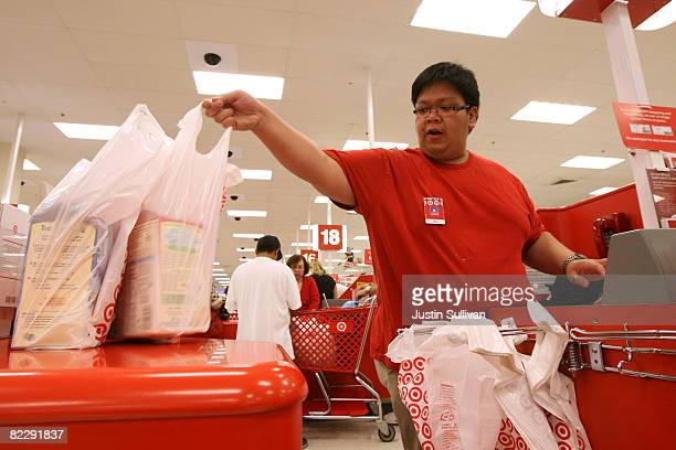 Target cashier Dino Pacheco bags items for a customer as he rings them up at a Target store August 13 2008 in Daly City California With stores...