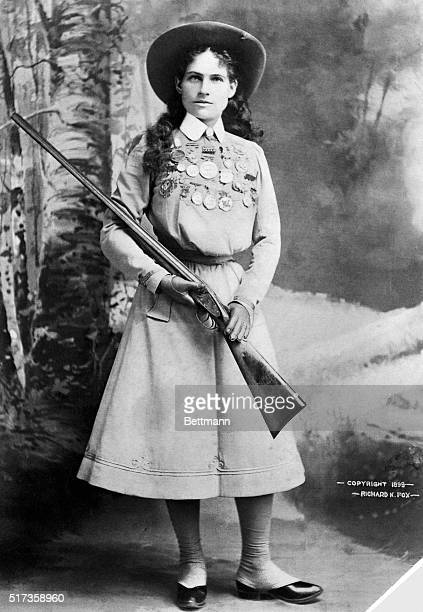 Target shooter Annie Oakley star of Buffalo Bill's Wild West show is shown holding a rifle