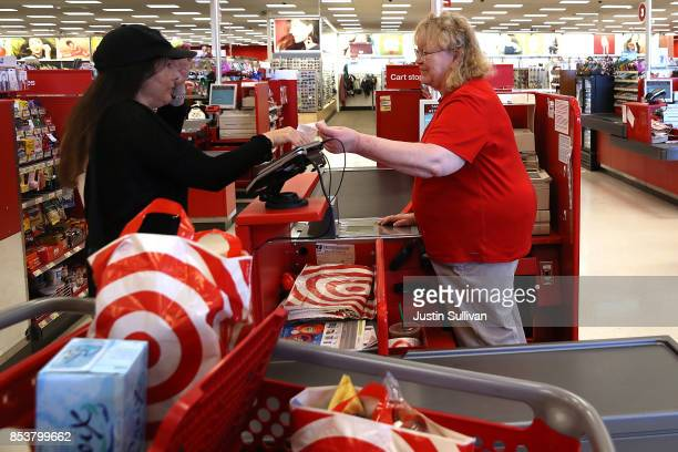 Target worker Ellen GibranHesse helps a customer at a Target store on September 25 2017 in San Rafael California Target Corp annouced plans to raise...