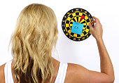 """A young woman throws a target at a dart board with a post-it note with the word """"ex"""" written on it. Target your ex-boyfriend. Getting even with your ex."""