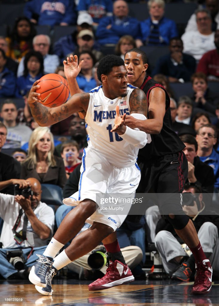 Tarik Black #10 of the Memphis Tigers drives against Kenyatta Smith #25 of the Harvard Crimson of the Harvard Crimson on January 19, 2013 at FedExForum in Memphis, Tennessee.
