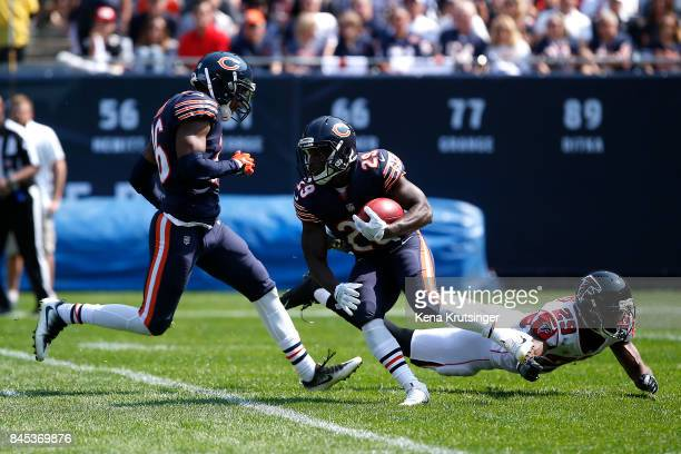 Tarik Cohen of the Chicago Bears carries the football past CJ Goodwin of the Atlanta Falcons in the first quarter at Soldier Field on September 10...