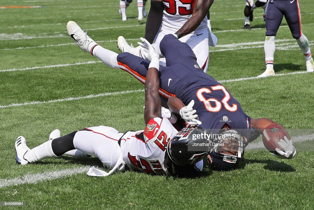 Tarik Cohen #29 of the Chicago Bears falls over Desmond Trufant #21 of the Atlanta Falcons to score his first NFL touchdown during the season opening game at Soldier Field on September 10, 2017 in Chicago, Illinois. The Falcons defeated the Bears 23-17.