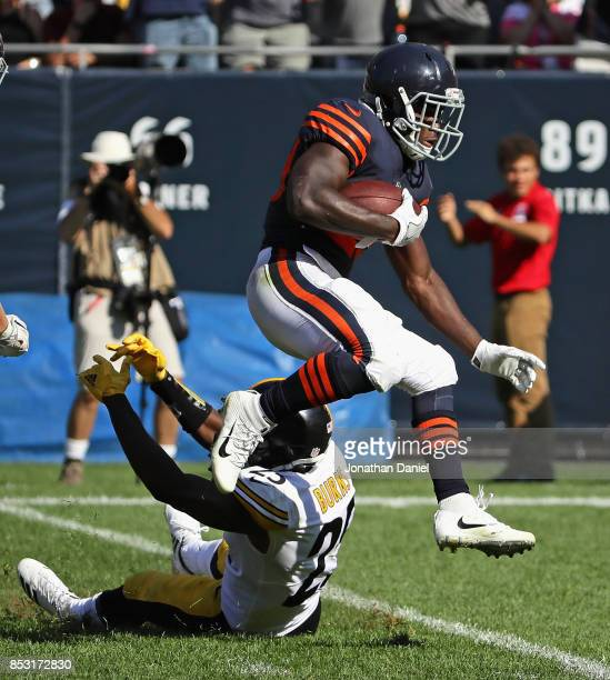 Tarik Cohen of the Chicago Bears leaps over Artie Burns of the Pittsburgh Steelers on a long run partially called back in overtime at Soldier Field...
