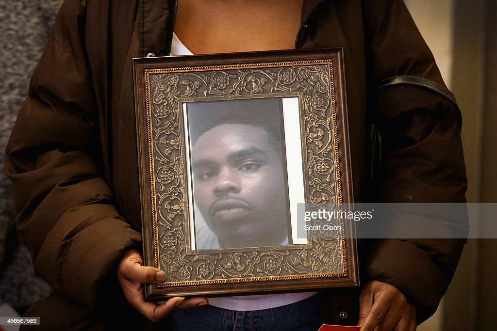 Tarinda Henderson holds a picture of her son Eddie Murphy during a gathering of gun violence victims and gun control advocates at Cornell Square Park on the anniversary of the Sandy Hook Elementary School shooting December 14, 2013 in Chicago, Illinois. Thirteen people, including a three-year-old boy, were wounded when gunmen opened fire on a crowd gathered at the basketball courts in Cornell Square Park in September. Twenty children and 6 adults were killed when a gunman opened fire at Sandy Hook School. Murphy, 21, was shot and killed on October 9, 2013. He was 1 of more than 400 people murdered in Chicago so far this year.