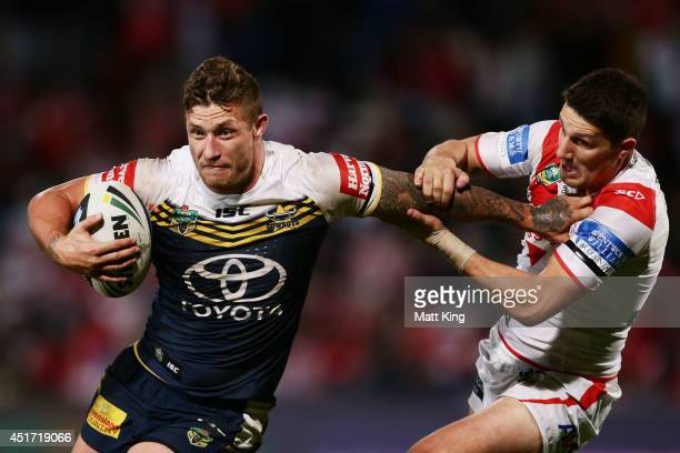 Tariq Sims of the Cowboys puts a fend on Gareth Widdop of the Dragons during the round 17 NRL match between the St George Illawarra Dragons and the...
