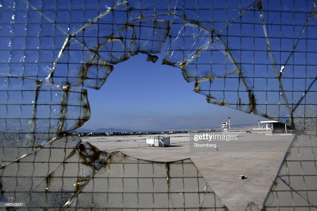 Tarmac at the abandoned east terminal of the former Athens International Airport is seen through a shattered glass window in the Hellenikon district of Athens, Greece, on Friday, Dec. 3, 2014. Hellenikon is the largest of Greece's land development projects, three times the size of the Principality of Monaco. Photographer: Kostas Tsironis/Bloomberg via Getty Images