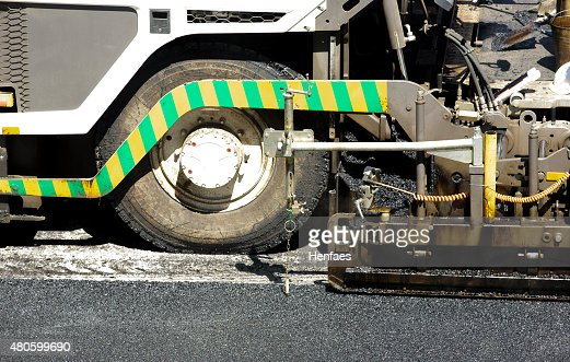 Tarmac being laid for a new road surface layer machine : Stock Photo