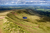 A view looking towards a Tarn (small mountain lake) from Corn du, within the Brecon Beacons National Park in South Wales. There is a large amount of clouds with a blue sky background. The scenery is m