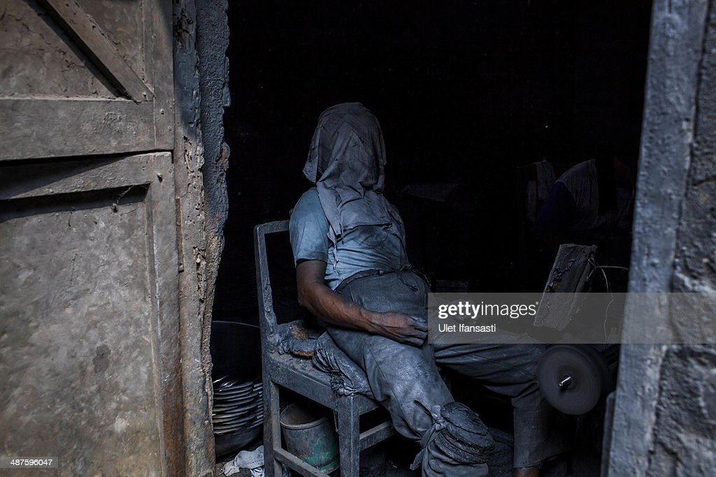 Tarno, a worker covers his face as he take a rest at Putra Logam workshop on May 1, 2014 in Yogyakarta, Indonesia. The pan polishers are paid around Rp. 40.000 (USD 3.46) per day. Today is International Labour Day, which aims to bring attention to working conditions, higher wages, and working hours across the world. Protesters across Indonesia have organised rallies to demand higher wages, as Indonesia recognises its first national labour day holiday.