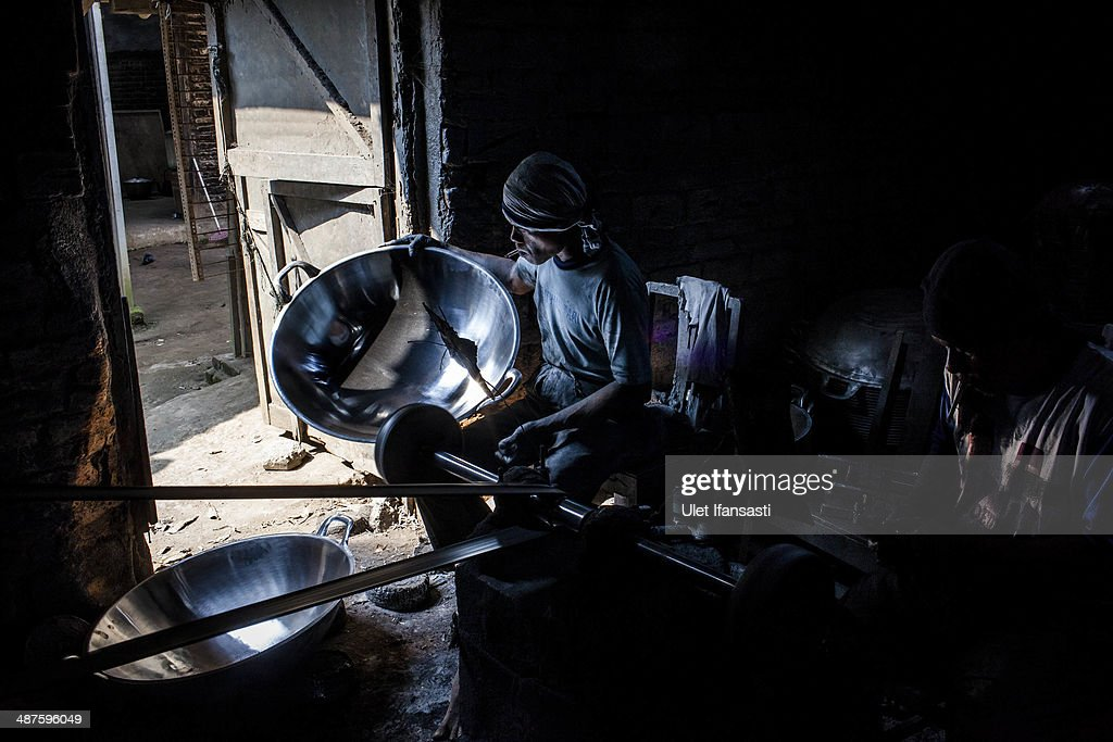 Tarno, a worker polishes a pan at Putra Logam workshop on May 1, 2014 in Yogyakarta, Indonesia. The pan polishers are paid around Rp. 40.000 (USD 3.46) per day. Today is International Labour Day, which aims to bring attention to working conditions, higher wages, and working hours across the world. Protesters across Indonesia have organised rallies to demand higher wages, as Indonesia recognises its first national labour day holiday.
